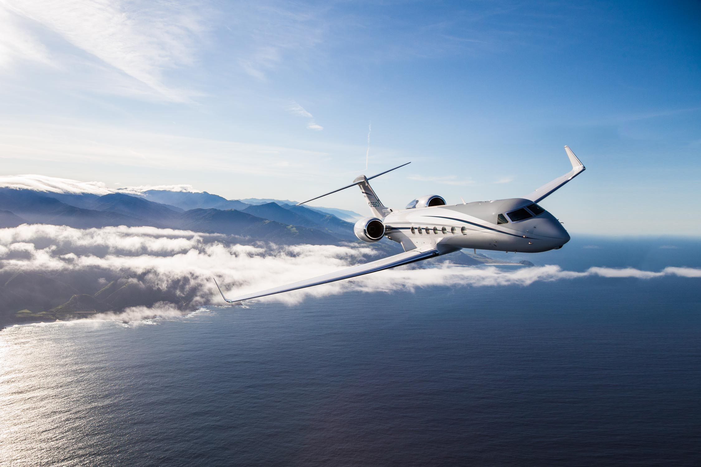 G550 flying above clouds and over water