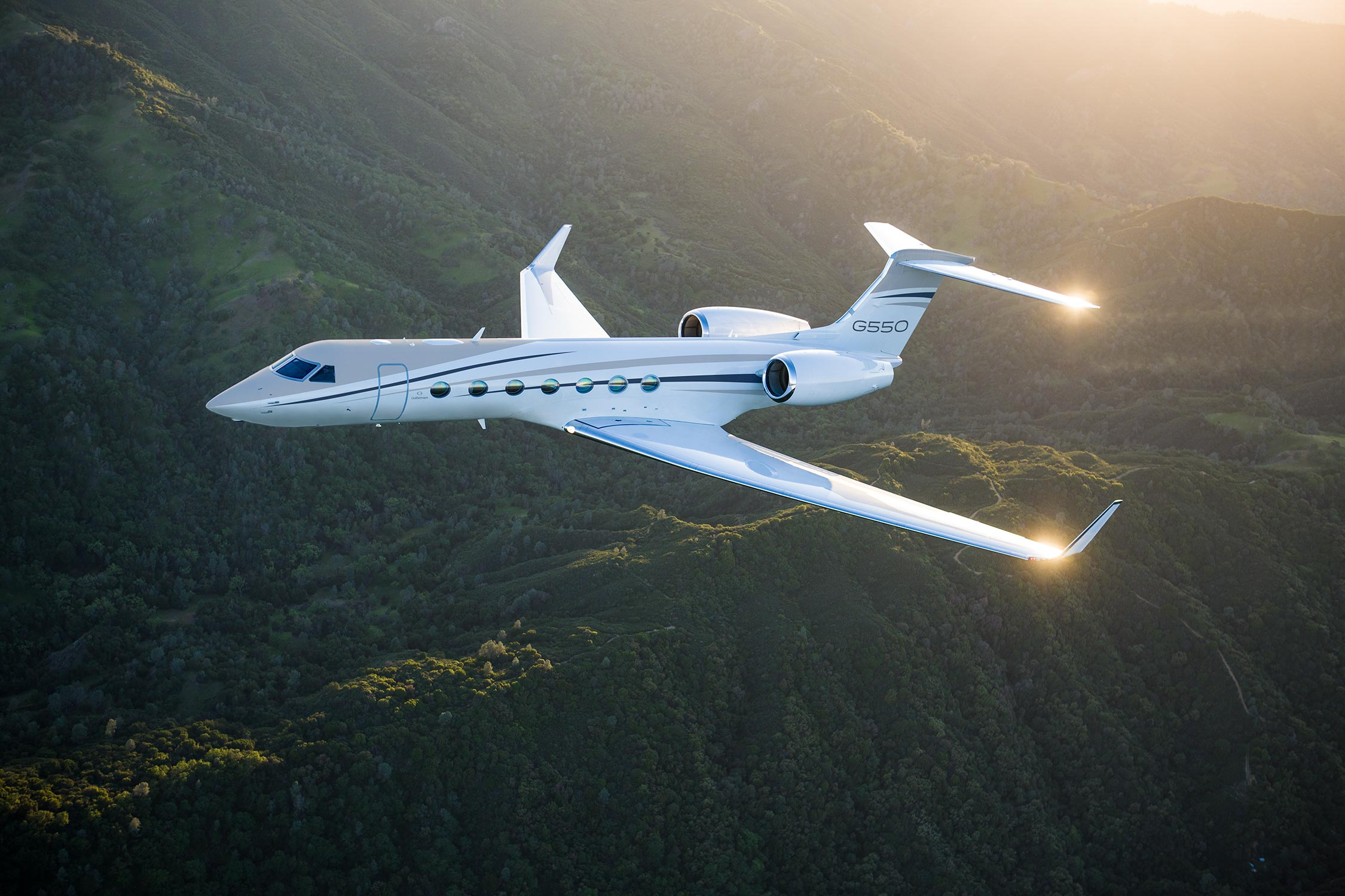 G550 flying over green mountains