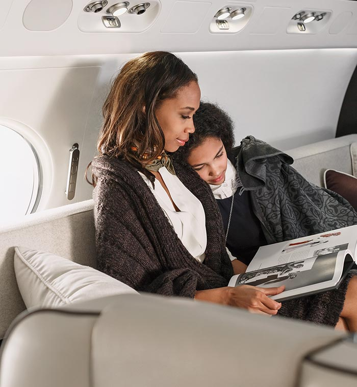 Mother reading to her daughter inside a private jet
