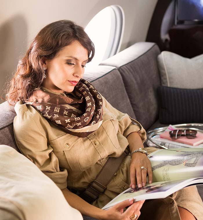 A woman reading a magazine in-flight