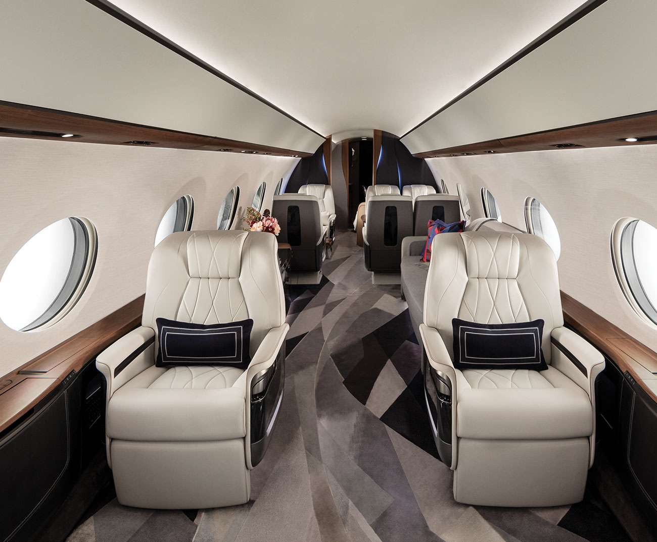 Two white leather chairs in luxury aircraft aisle