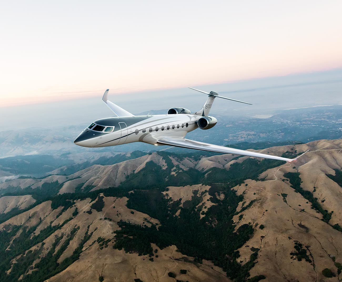 G700 flying over mountains