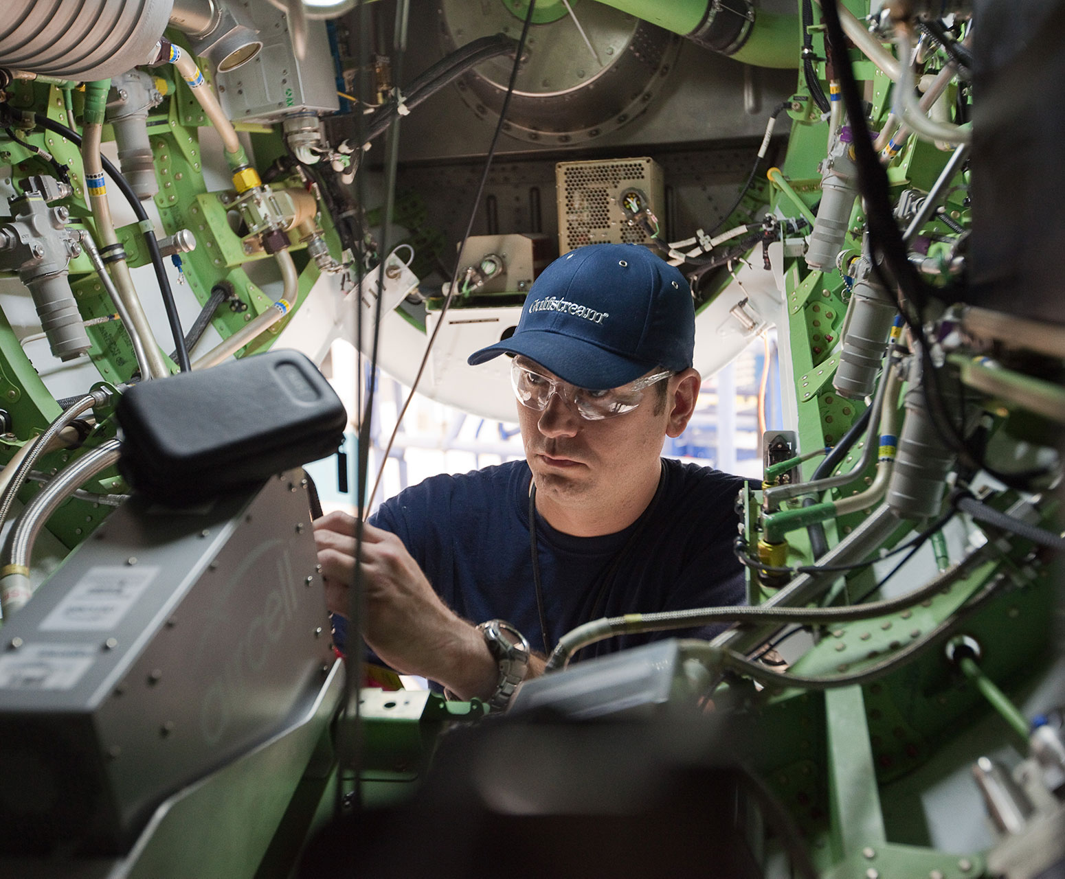 Technician with hat working on electronics inside aircraft