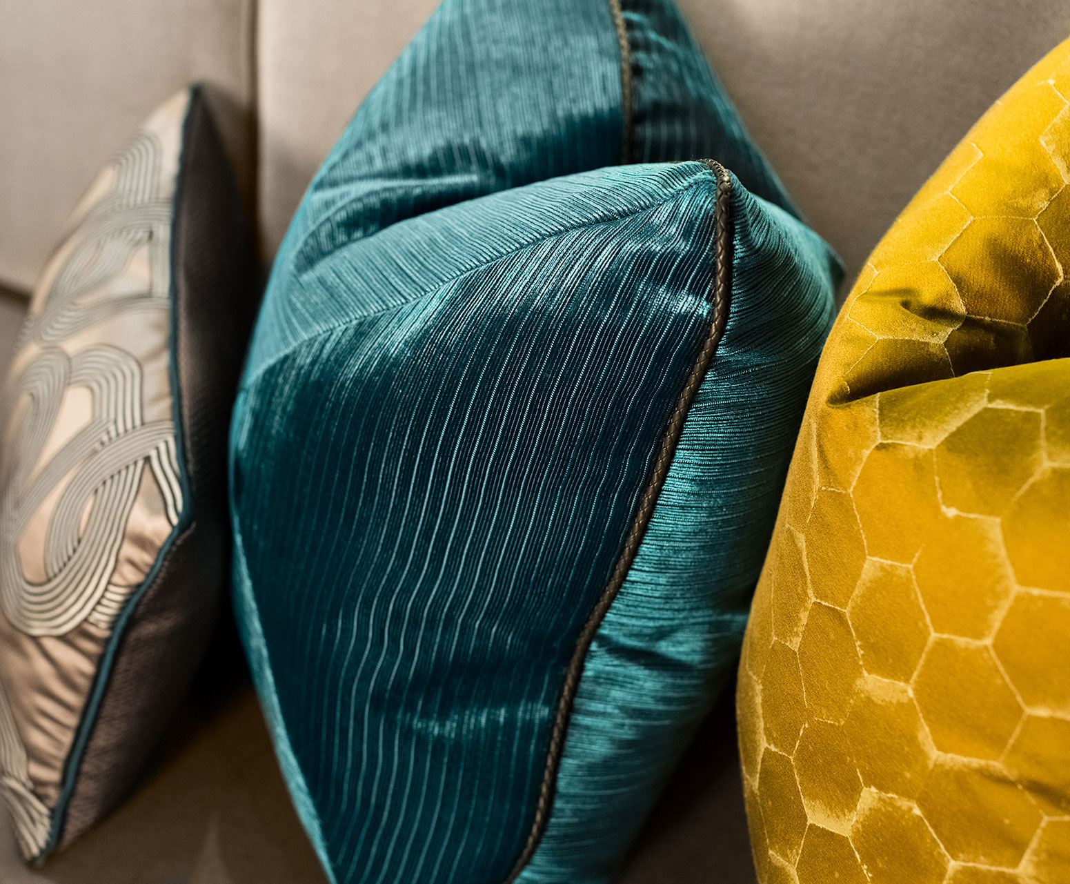 Gray, aqua and yellow luxurious pillows on a couch.
